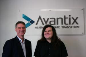 Liam and Duncan stand in front of the Avantix sign