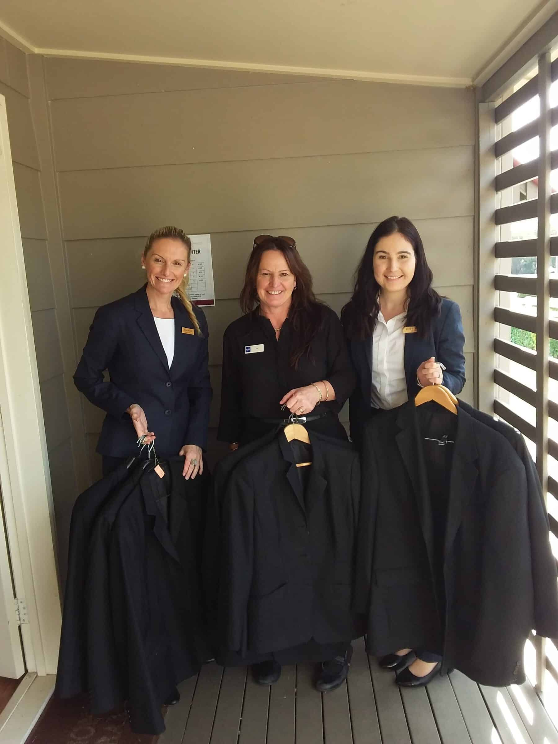 Traditional Funerals employees stand together holding donated uniforms