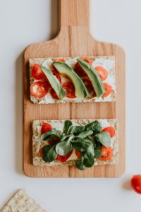 Sandwich thins with avocado and tomatoes in a wooden serving board.