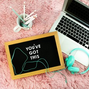 "A laptop on a pink rug with a sign that says ""you've got this"""