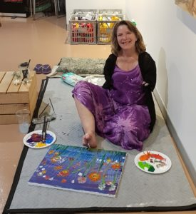 Artist Trish Jackson sits on the ground holding a paintbrush with her foot. A canvas painting is in progress.