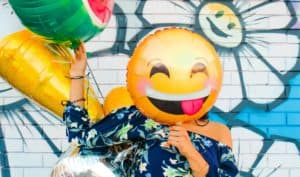 A woman covering her face with a winking emoji balloon. She also holds a watermelon balloon.