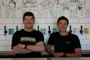 Two men pose behind a bar at Brouhaha brewery