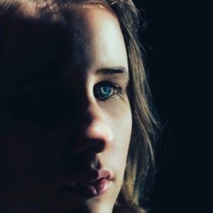 Close up of a young women's face, half in darkness