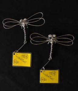 Two wire dragonfly sculptures on a black background