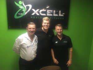 Pat, Clancy and Jason standing together in front of a green wall and a 'Xcell health fitness' sign