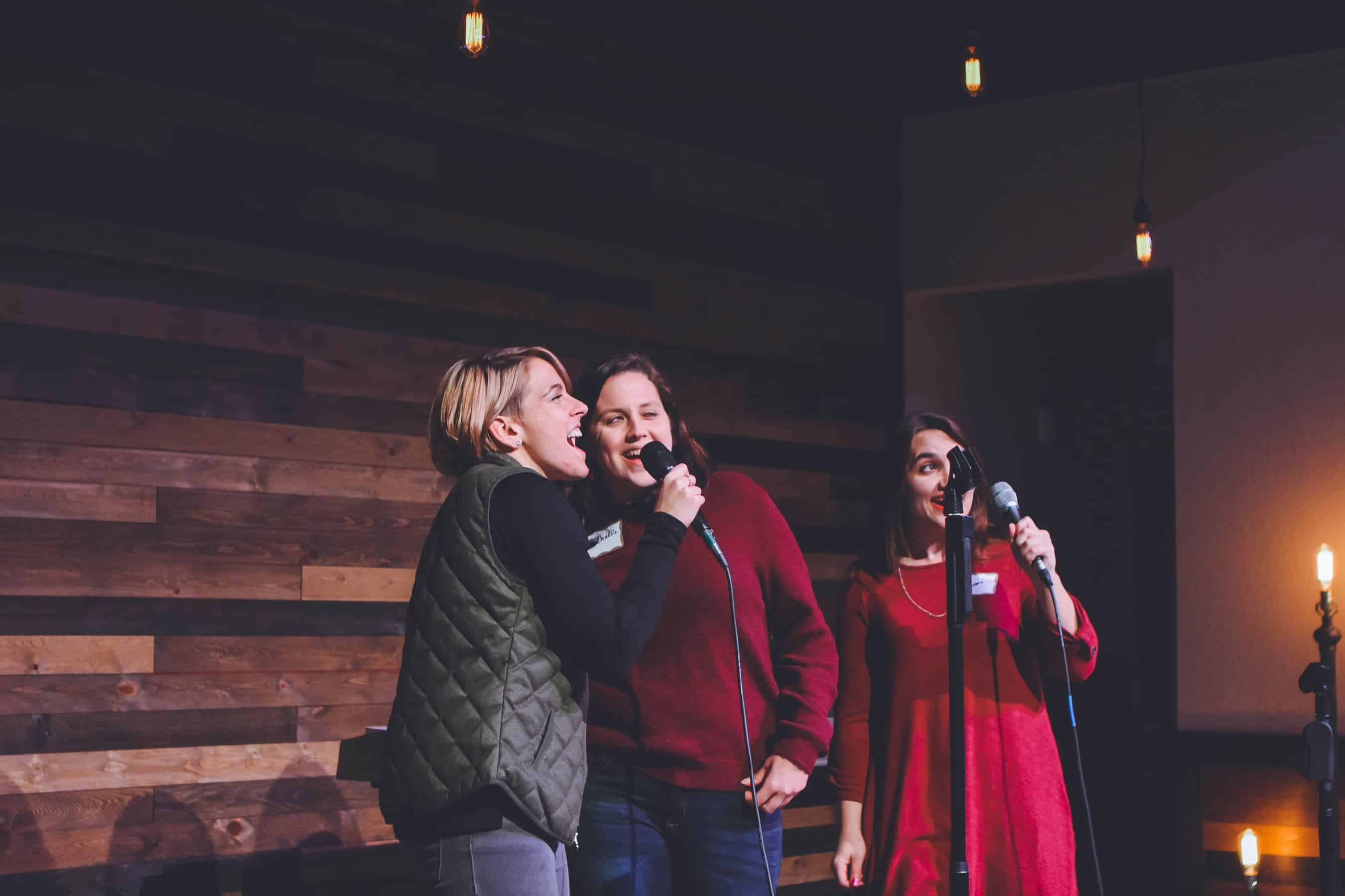 Three women stand on a stage and sing into microphones.