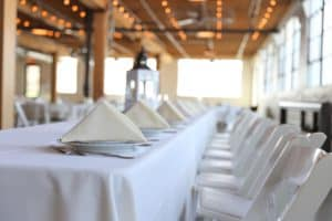 Long table with a white table cloth and folded, triangular napkins at each seat.
