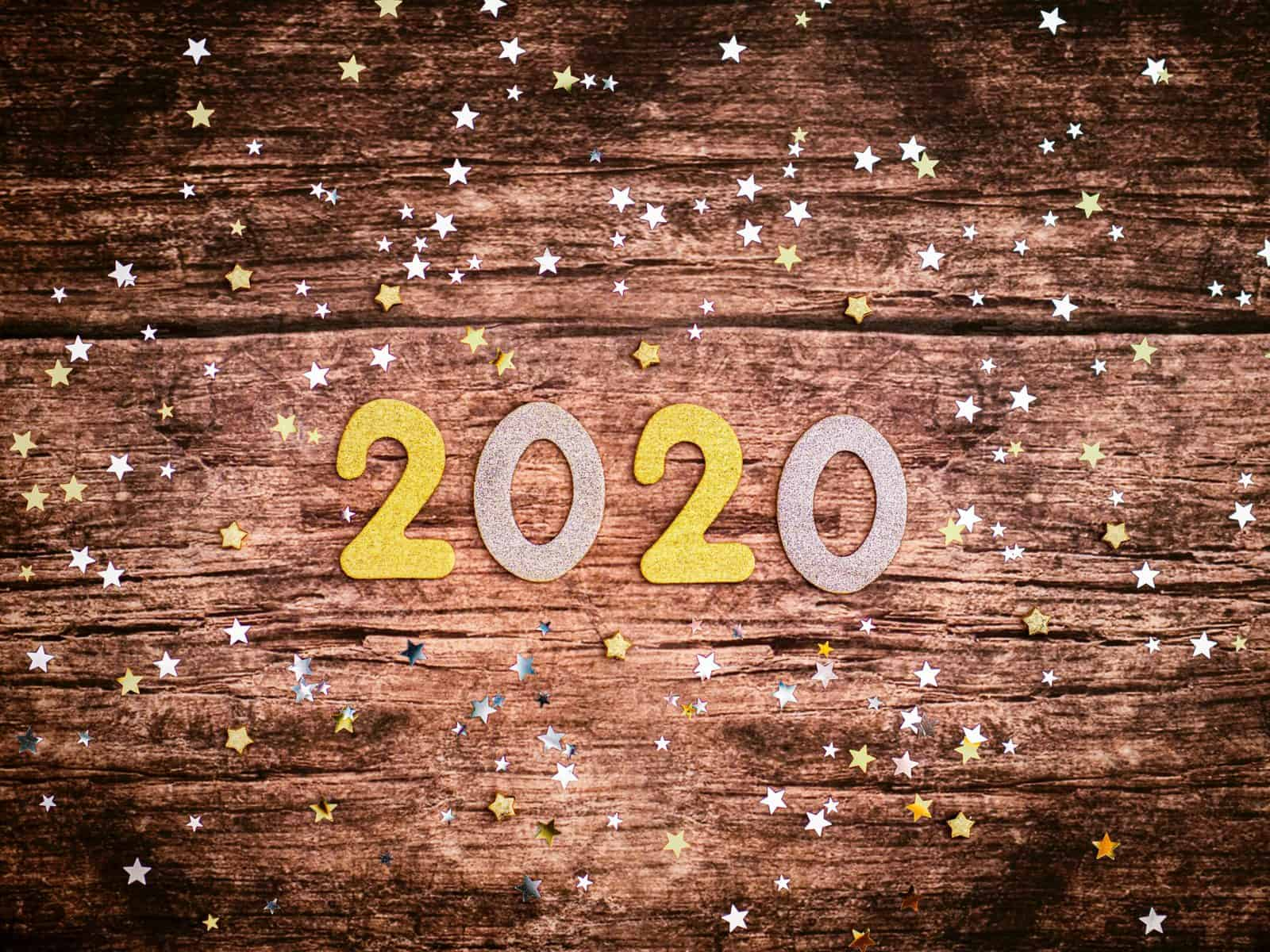 a wooden table top with the text 2020 in yellow and silver. Glitter is scattered on the table