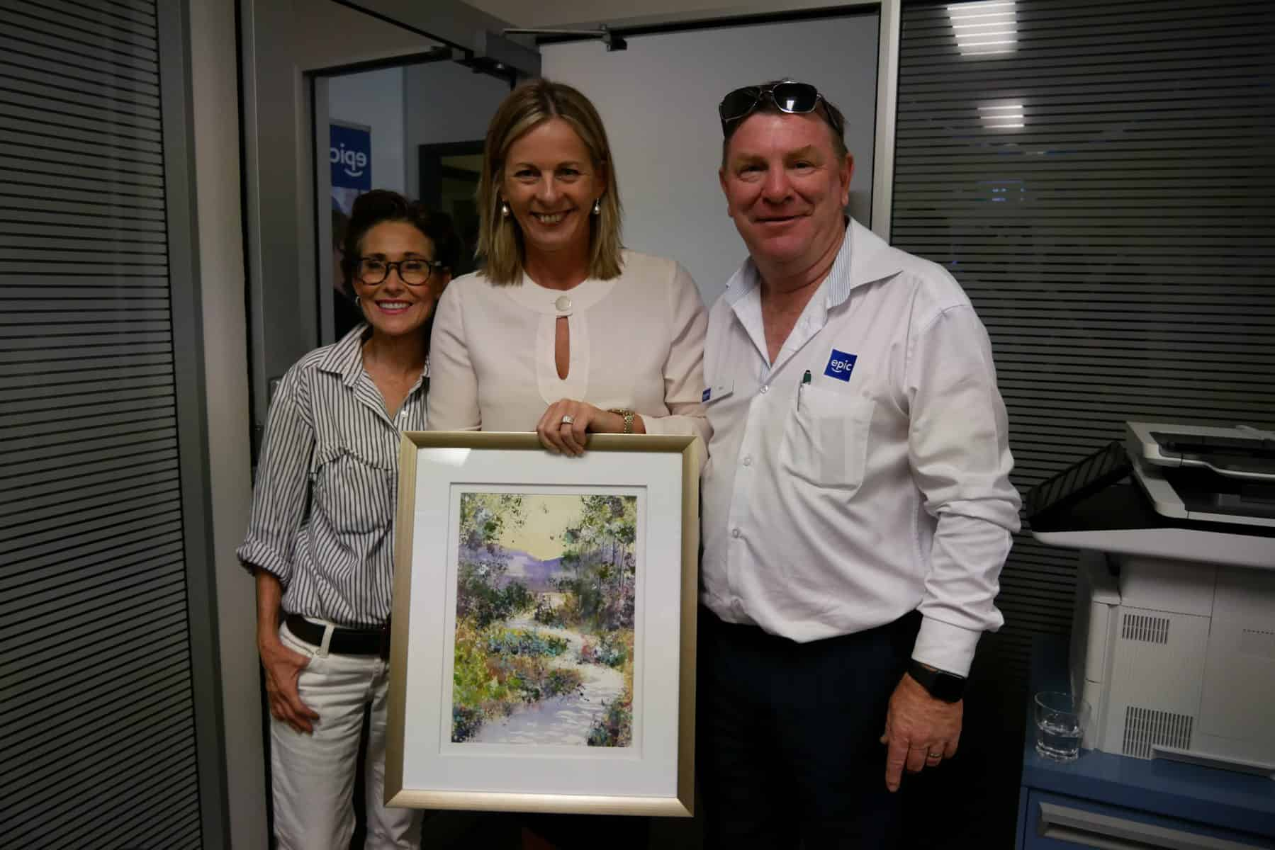 Helene, MP Angie Bell and EPIC employee Pat stand together holding Helene's artwork