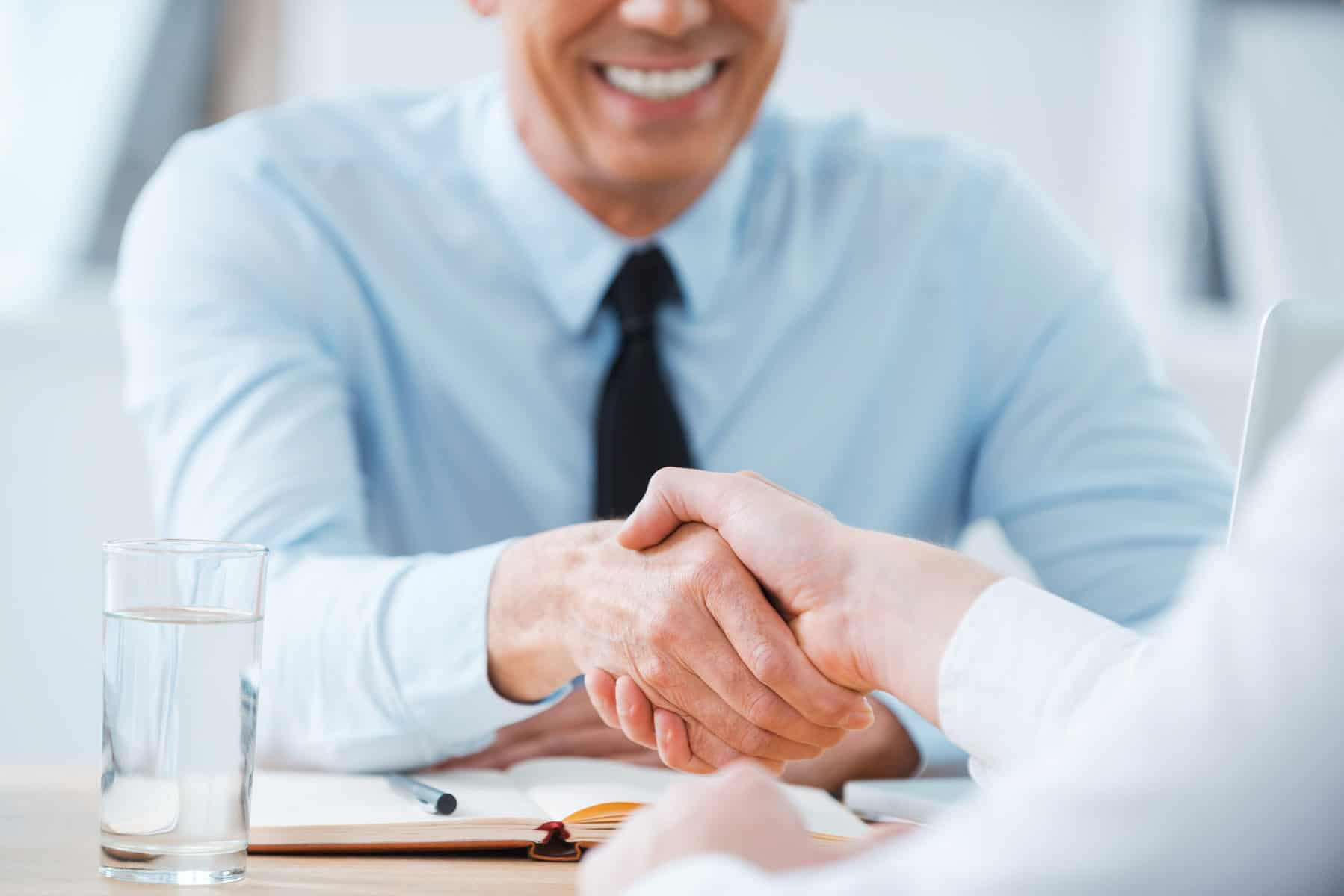 Man in business shirt and tie shaking a hand across a table