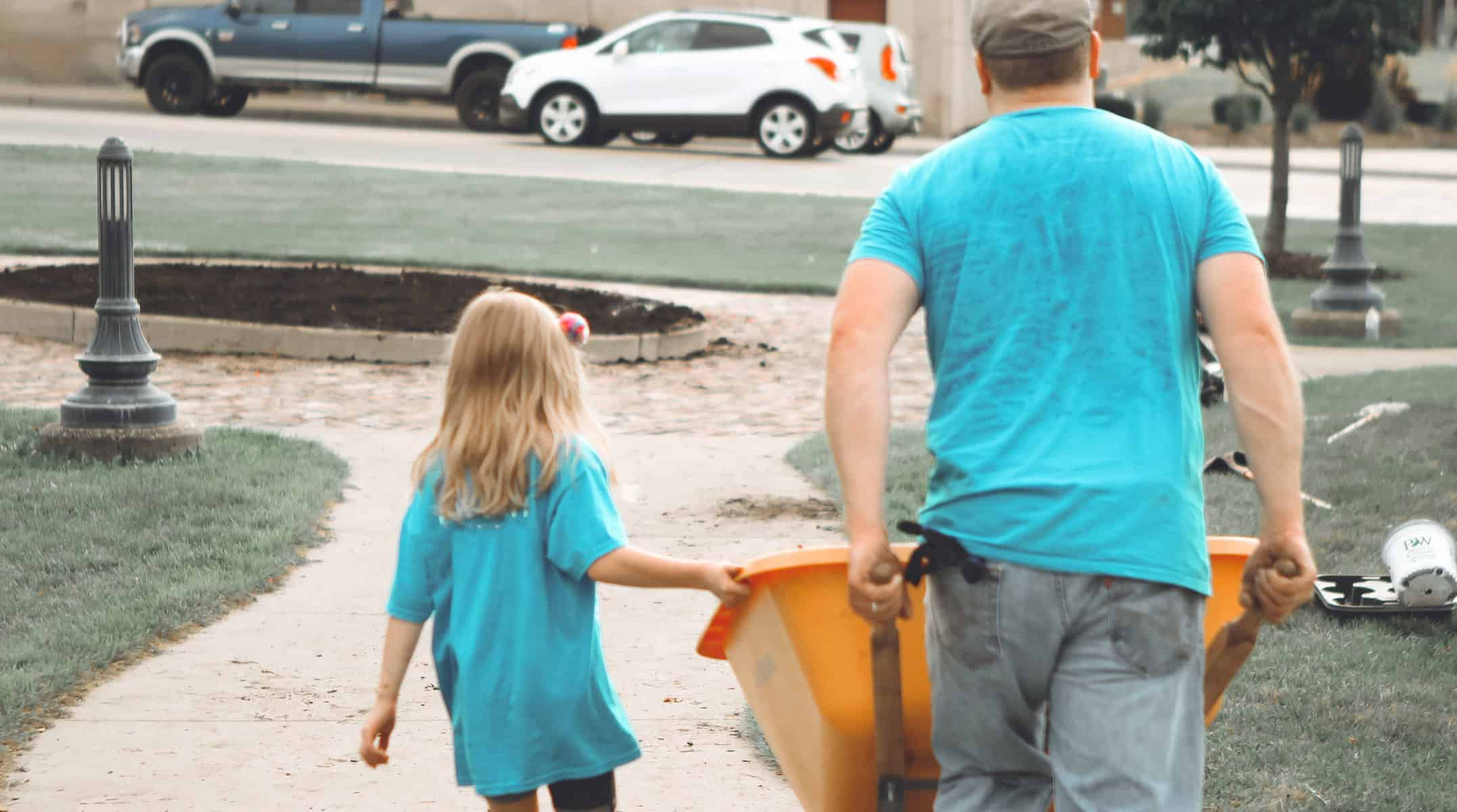A father and daughter volunteer by moving a wheelbarrow.