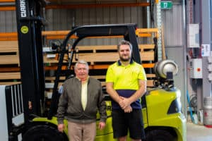 Employer Alan Bull and employee Brett Wilson stand in front of a forklift at supportive workplace Cutting Edge Cabinets