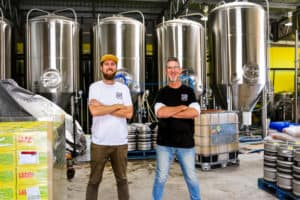 Two men stand with their arms folded in the middle of supportive employer Your Mates brewery